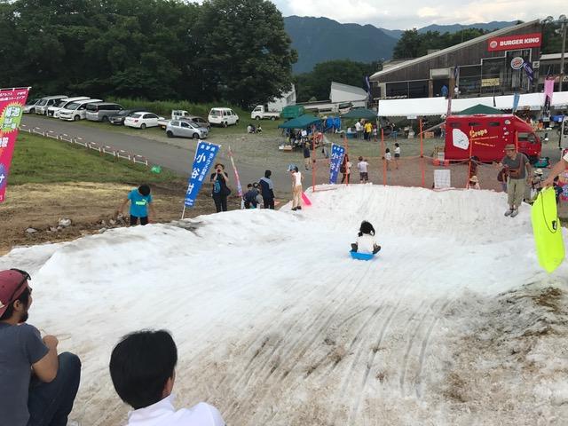真夏の雪の斜面ソリ遊び