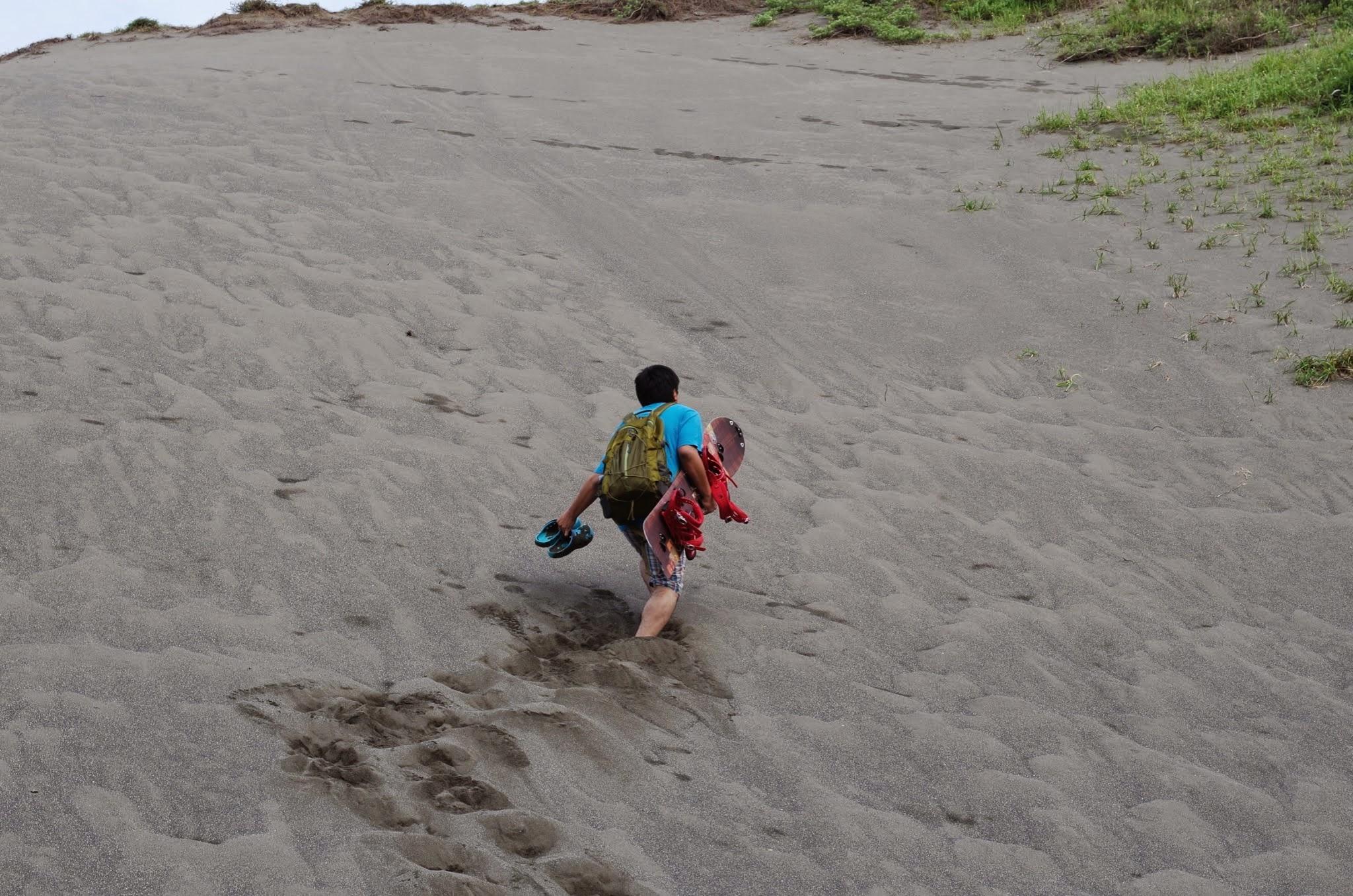 砂山をスノーボードを持って登る姿