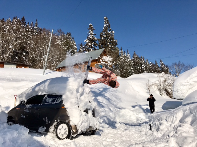 スノーボードで屋根雪を落とす